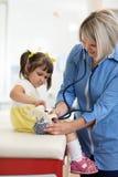 Behandeln Sie Untersuchungsspielzeug und das kleine Mädchen, das Stethoskop verwendet Stockbild