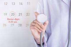 Behandeln Sie Verabredungskonzepthintergrund mit Anmerkung über Kalender und behandeln Sie die Hand, die Stethoskop hält lizenzfreie stockbilder