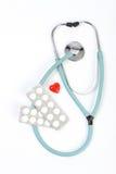 Behandelt blaues Stethoskop, Pillen und ein kleines rotes Herz auf weißem Hintergrund Lizenzfreies Stockbild