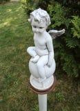 Behandla som ett barn ängeln - skulptera i trädgården på den Hodos-Bodrog kloster - Arad, Rumänien royaltyfri bild