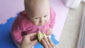 Behandla som ett barn äta avokadot från händer för moder` s lager videofilmer