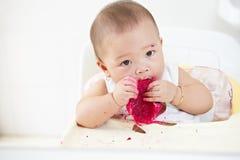 Behandla som ett barn äta drakefrukt Arkivfoto