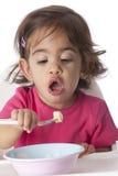 behandla som ett barn äta flickan hon själv Arkivfoton