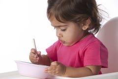 behandla som ett barn äta flickan hon själv Royaltyfri Bild