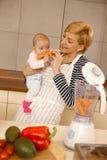 Behandla som ett barn äta moroten med modern Royaltyfria Foton