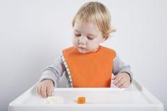Behandla som ett barn äta ris och moroten Arkivfoto