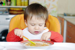Behandla som ett barn äta soppa på kök Royaltyfria Bilder