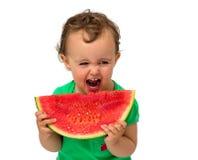 behandla som ett barn äta vattenmelonen Arkivbild