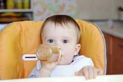 Behandla som ett barn åldern av 1 år drinkar från den lilla flaskan Arkivfoto