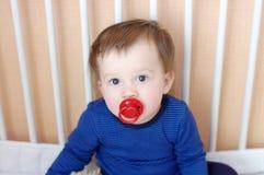 Behandla som ett barn åldern av 1 år med fredsmäklaren i vit säng Arkivfoto