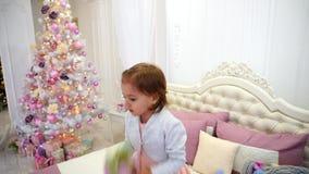 Behandla som ett barn året och banhoppningen för flicka det lyckliga nya på säng i rum för barn` s på den rosa bakgrundsjulgranen stock video