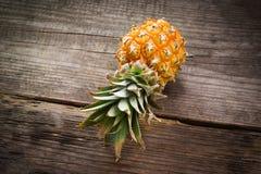 Behandla som ett barn ananas på en trätabell. Arkivfoton