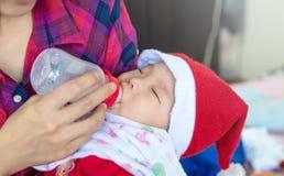 Behandla som ett barn att äta mjölkar från flaskan på moder matar hennes nyfödda Bab Royaltyfria Foton