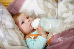 behandla som ett barn att dricka för flaska mjölkar Behandla som ett barn av 4 månader som rymmer flaskan själv Arkivbilder