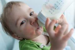 behandla som ett barn att dricka för flaska mjölkar rymma sig sött roligt Royaltyfri Fotografi