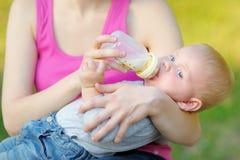 Behandla som ett barn att dricka mjölkar från flaskan i moderhänder Royaltyfri Bild
