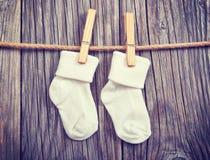 behandla som ett barn att hänga för klädstreckgodor Behandla som ett barn vita sockor på en klädnypa Royaltyfria Foton