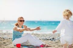 behandla som ett barn att leka för strandmom Arkivbild