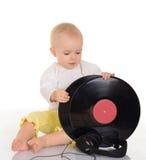 Behandla som ett barn att leka med det gammal vinylrekordet och hörlurar Arkivfoton