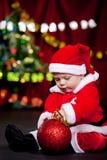 Behandla som ett barn att leka med julbollen Royaltyfria Foton