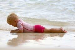 Behandla som ett barn att ligga på stranden arkivfoto