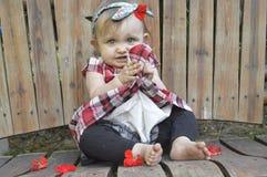 Behandla som ett barn att posera för flicka som är förtjusande på wood gungainnehavblommor Arkivbild