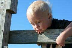 Behandla som ett barn att se in i vatten från träbron Royaltyfri Fotografi