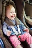 Behandla som ett barn att sitta lyckligt i bilsäte Arkivbild