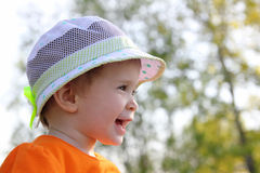 behandla som ett barn att skratta för hatt som är utomhus- Fotografering för Bildbyråer