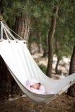 Behandla som ett barn att sova i hängmatta Arkivfoto