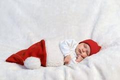 Behandla som ett barn att sova i jultomtenhattar Arkivfoto