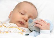 Behandla som ett barn att sova i säng Arkivbild