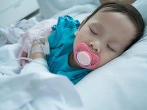 Behandla som ett barn att sova i sjuksäng i sjukhus, i att motta som är intravenöst Royaltyfria Bilder