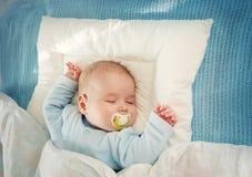 Behandla som ett barn att sova på den blåa filten Royaltyfria Foton