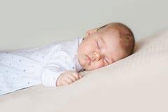 Behandla som ett barn att sova på den vita sängen Arkivbild