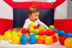 Behandla som ett barn att spela med färgrika bollar Arkivfoto