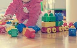 Behandla som ett barn att spela med färgrika tegelstenar på trägolv Arkivfoto