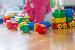 Behandla som ett barn att spela med färgrika tegelstenar på trägolv Arkivbild
