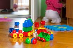 Behandla som ett barn att spela med färgrika tegelstenar på trägolv Fotografering för Bildbyråer