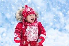 Behandla som ett barn att spela med insnöad vinter royaltyfria bilder