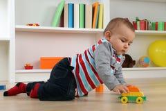 Behandla som ett barn att spela med leksakbilen Arkivfoton