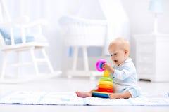 Behandla som ett barn att spela med leksakpyramiden Ungelek royaltyfria bilder
