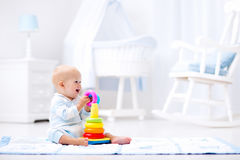 Behandla som ett barn att spela med leksakpyramiden Ungelek royaltyfri bild