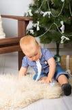 Behandla som ett barn att spela nära julgranen Arkivbilder