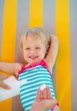 Behandla som ett barn att vänta medan modern som applicerar sunblockkräm Arkivbilder