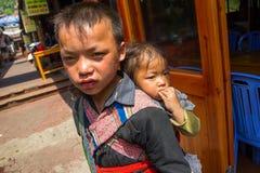 Behandla som ett barn bära för den Unidenti oidentifierat Hmong pojken i Sapa, Lao Cai, Vietnam Arkivbild