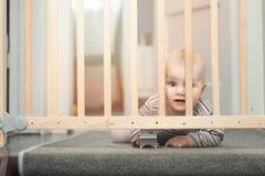 Behandla som ett barn bak säkerhetsportar framme av trappa arkivbild