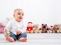 Behandla som ett barn barfota på vit bakgrund med keliga leksaker - gulligt litet Arkivfoto