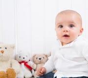 Behandla som ett barn barfota på vit bakgrund med keliga leksaker - gulligt litet Arkivbilder