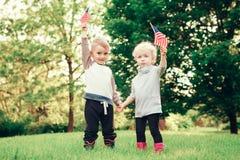 Behandla som ett barn barn med amerikanUSA-flaggor Fotografering för Bildbyråer